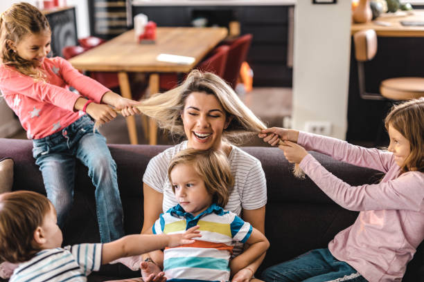 playful kids having fun with their nanny at home. - puxar cabelos imagens e fotografias de stock