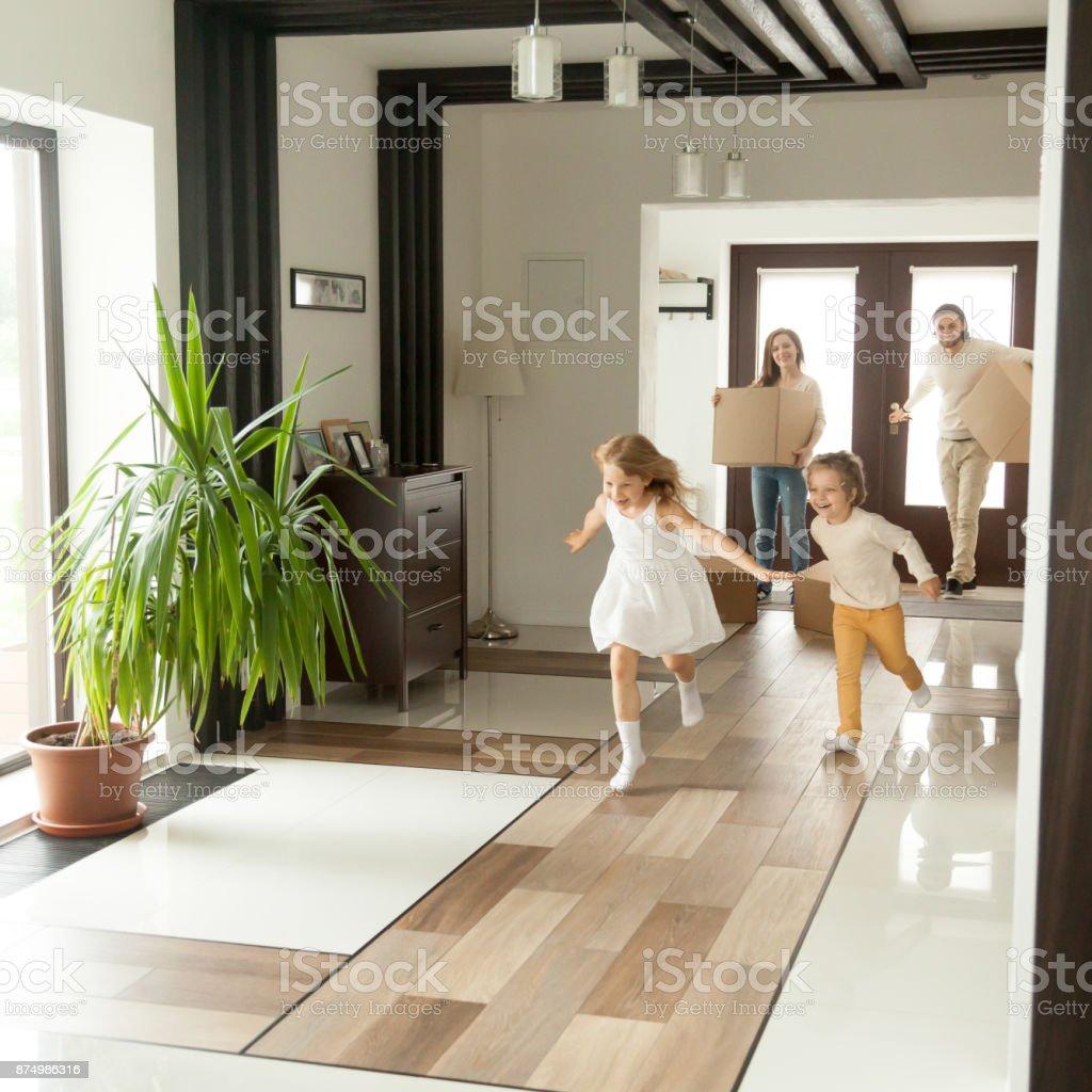 Niños juguetones corriendo en casa nueva, en el concepto de familia - foto de stock