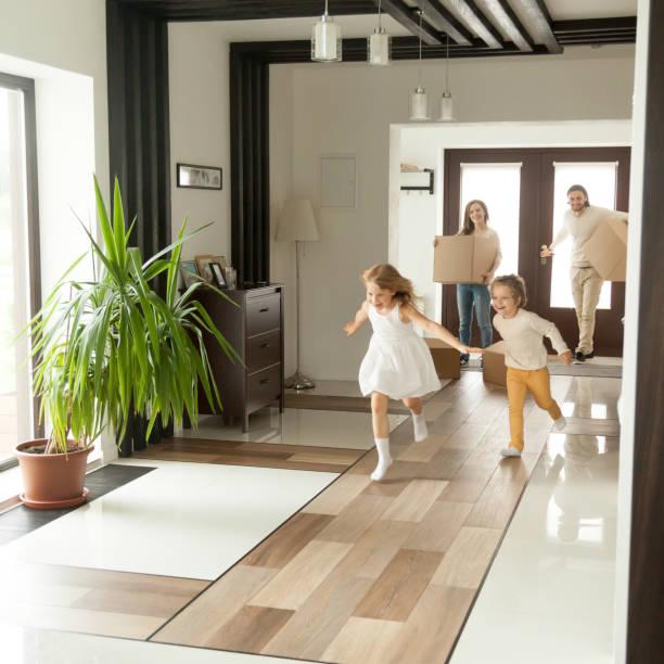 Lúdicas crianças correndo em casa nova, movendo-se no conceito de família - foto de acervo