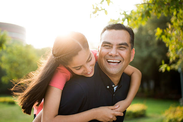 Playful latin father and teen daughter laughing stock photo