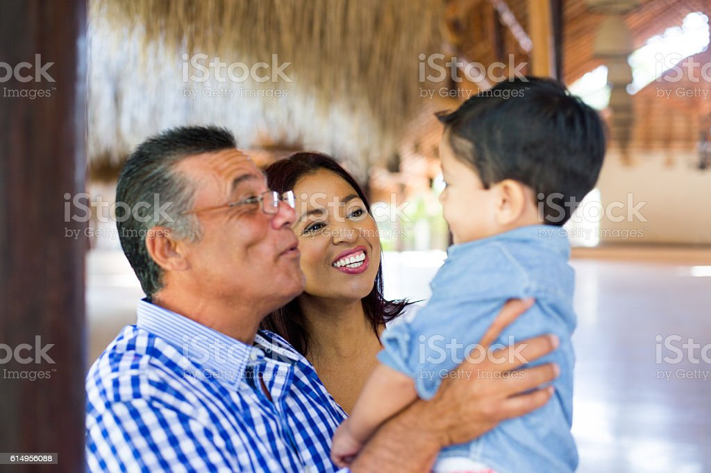 Playful latin grandparents holding grandson and smiling at him - foto de stock