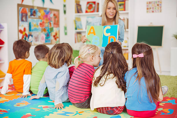 Playful learning Teacher with a group of preschool children in a nursery. The children are sitting on the floor and listening  teacher. Learning letters. In the background we can see a shelf with some, toys, black board and books. View from behind. preschool age stock pictures, royalty-free photos & images