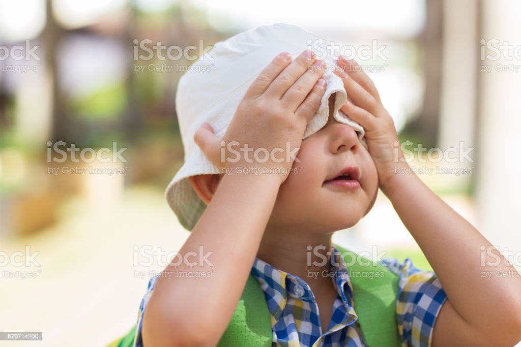 Playful Little Boy Covering Eyes With Hands stock photo