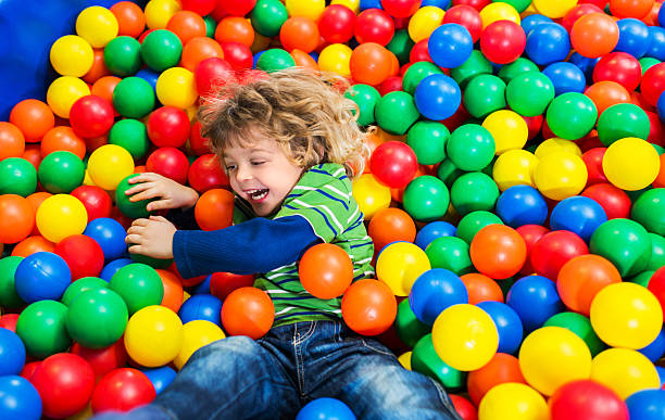 Playful little boy in playroom. stock photo