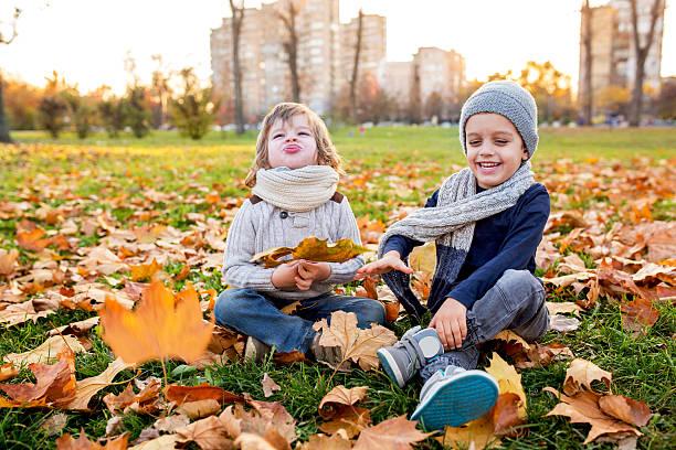 playful little boys having fun in autumn park. - mini amusementpark stockfoto's en -beelden