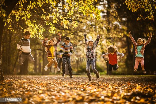 Large group of playful kids having fun while jumping during autumn day in nature. Copy space.