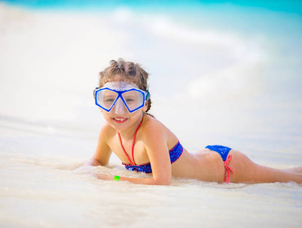 playful little girl enjoying on maldivies bech - girl alone in swimsuit stock photos and pictures