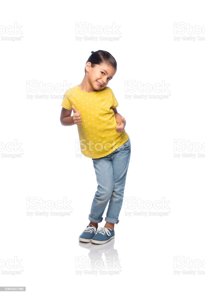 Playful little girl giving thumbs up stock photo