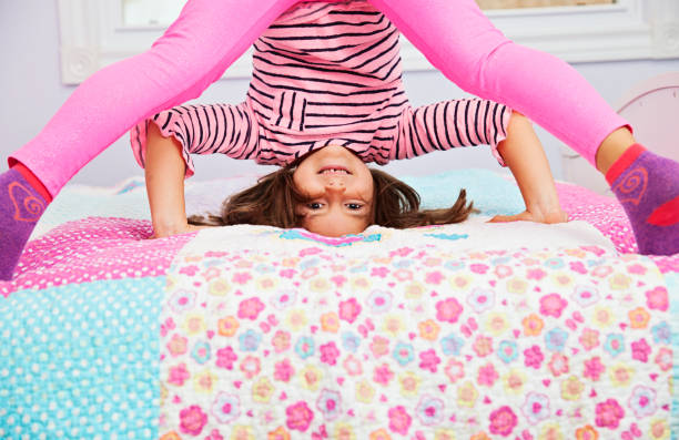 Playful little girl goofing around in her bedroom stock photo
