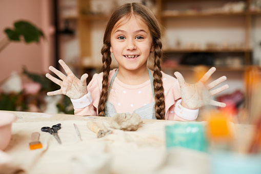 Playful Little Girl in Pottery Class