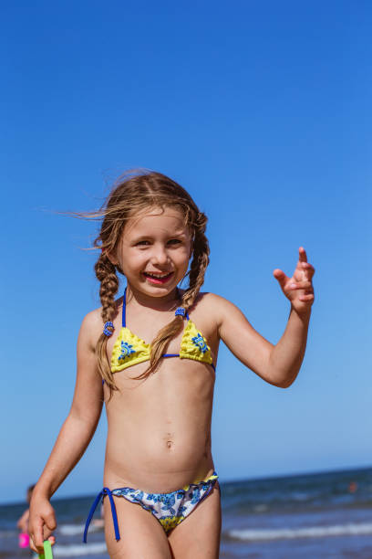 playful little girl on sandy  beach - girl alone in swimsuit stock photos and pictures