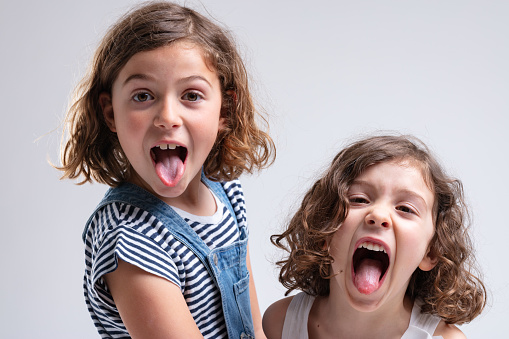 Playful Little Girls Sticking Out Their Tongues Stock