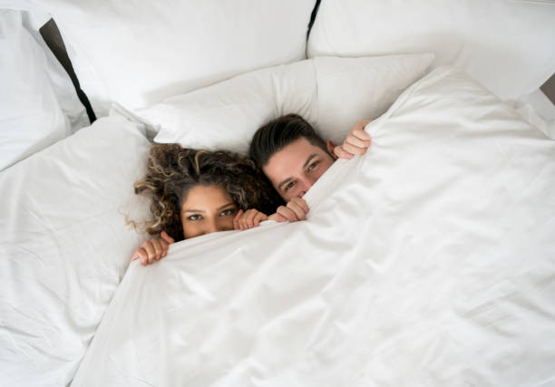 Playful loving couple in the bed Portrait of a playful loving couple in the bed covering with the duvet - relationship concepts couple in bed stock pictures, royalty-free photos & images