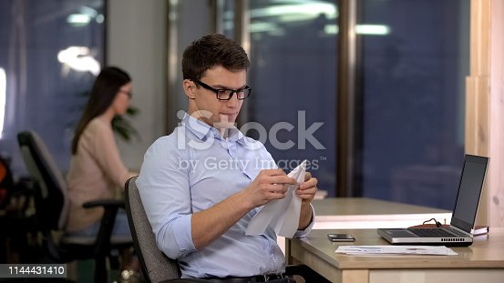 593328060istockphoto Playful male making paper plane in office, tired monotonous routine work, break 1144431410