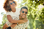 Young man giving piggyback ride to woman. Cheerful couple enjoying summer vacation in city. They are wearing sunglasses.