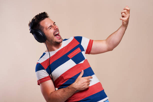 Playful man listening to music and playing air guitar stock photo