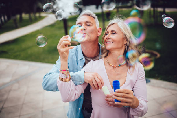 Playful mature couple blowing bubbles at the park stock photo