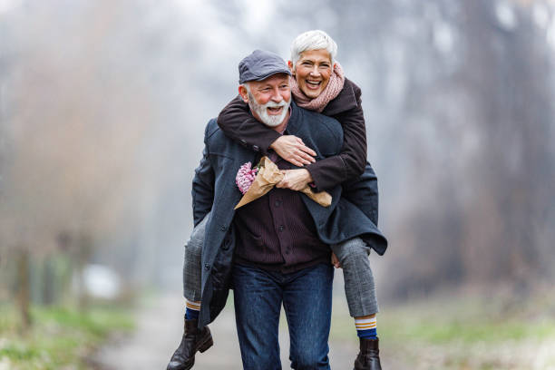 Playful mature couple piggybacking in winter day. stock photo