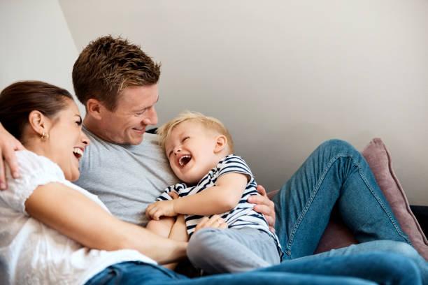 Verspielte mittlere erwachsene Eltern kitzeln Sohn zu Hause – Foto