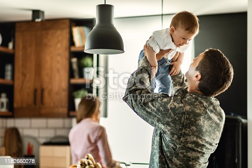 Happy baby boy having fun with his military dad at home. Mother is in the background.