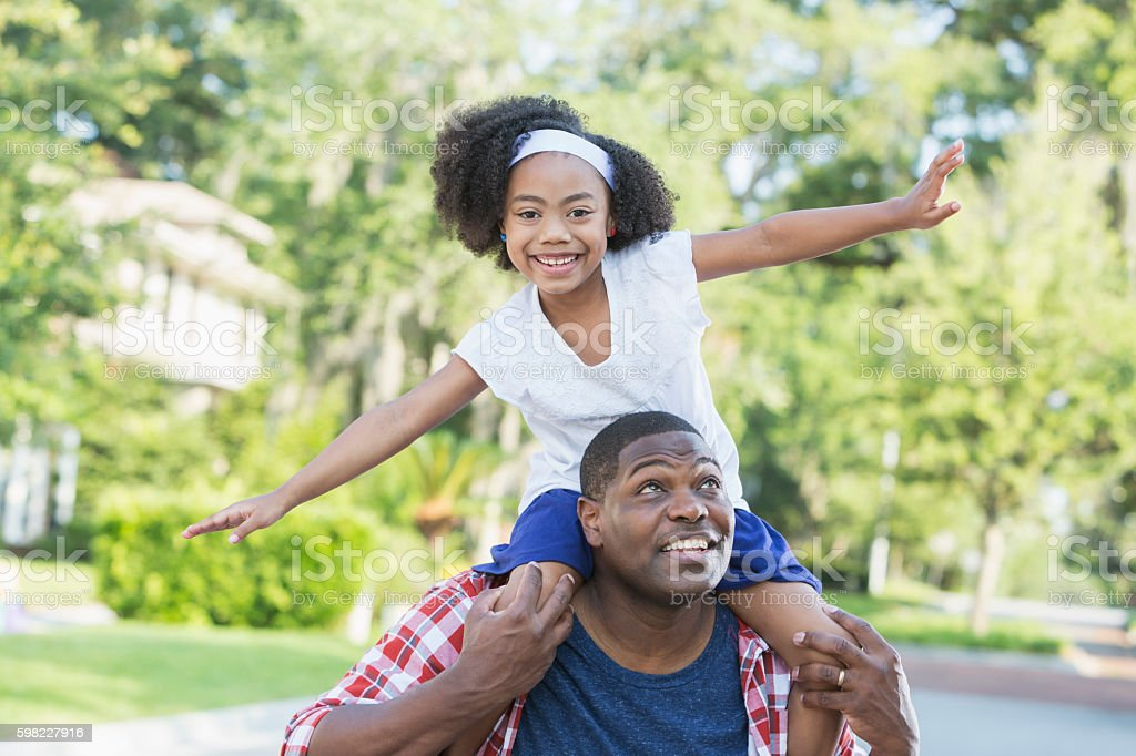 Playful mixed race girl sitting on father's shoulders foto royalty-free
