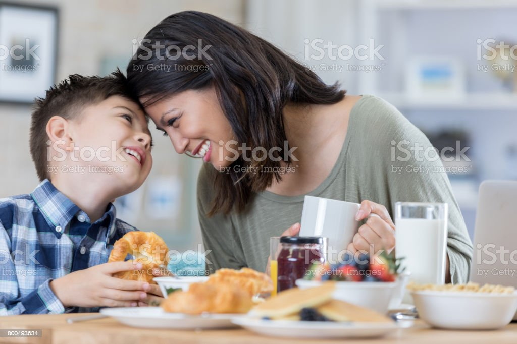 Playful mom enjoys breakfast at home with her son stock photo