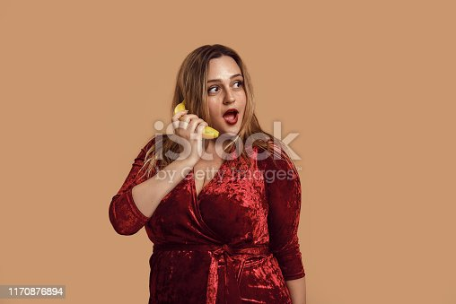 Playful mood. Studio shot of plus size smiling woman in red velour dress holding banana near her ear and representing conversation on phone. Carefree time. Overweight female. Xxl model