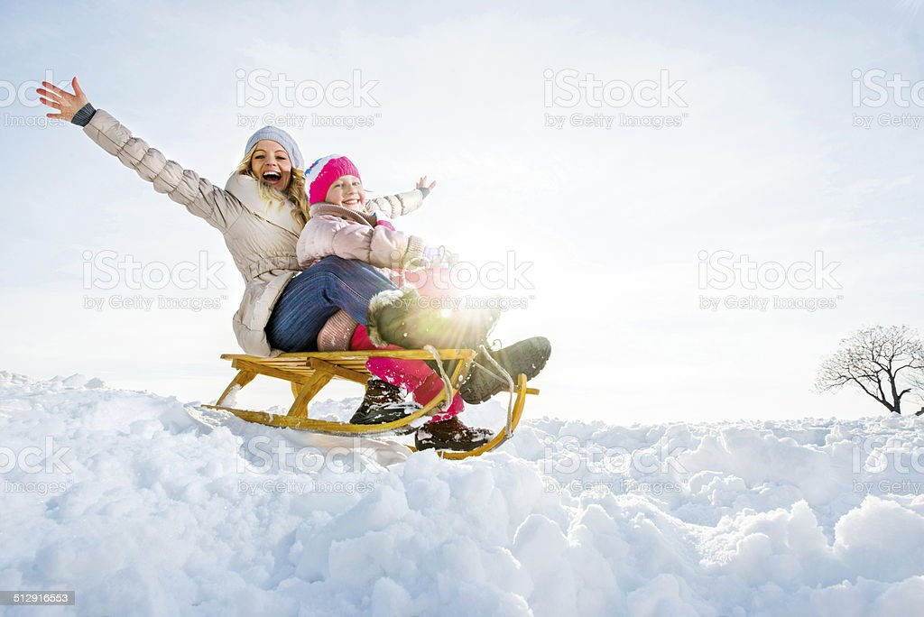 Playful mother and daughter in winter. stock photo