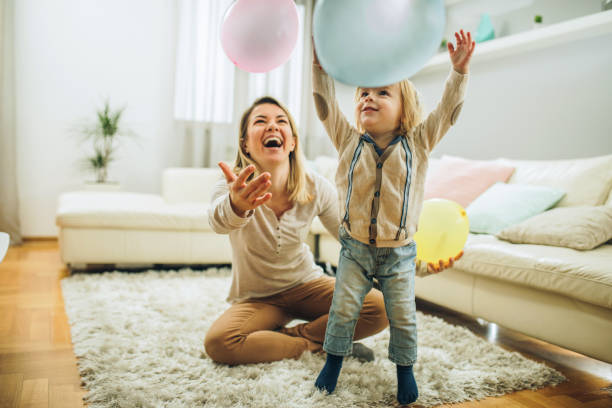 Playful mother and son having fun with balloons in the living room. stock photo