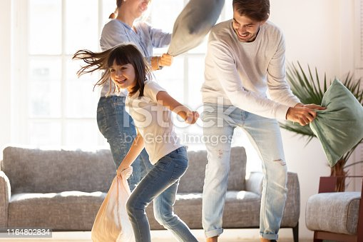 Playful young parents have fun with little preschooler daughter engaged in pillow fight in living room, happy family relax playing with small girl child, enjoy spending time at home together