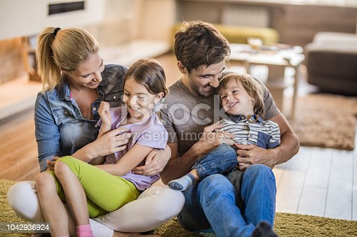 1159543952istockphoto Playful parents having fun while tickling their kids at home. 1042936924
