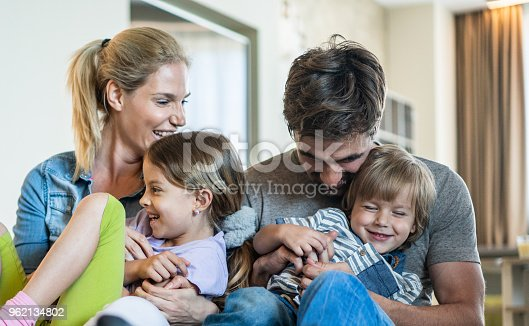 1159543952istockphoto Playful parents having fun while tickling their kids at home. 962134802