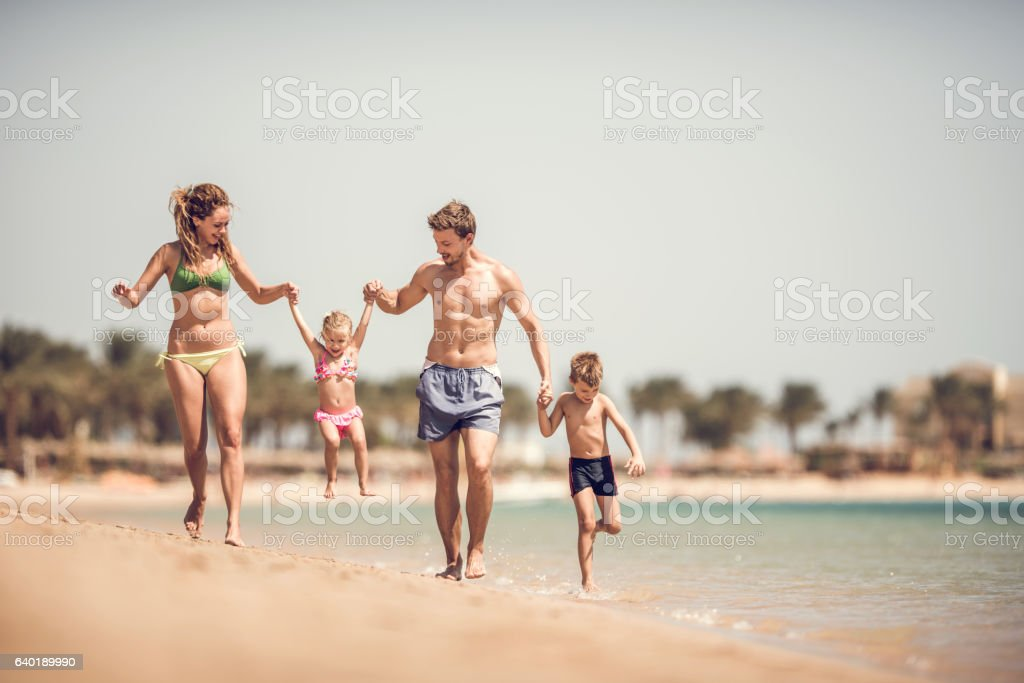 Playful parents having fun with their small kids in summer. stock photo