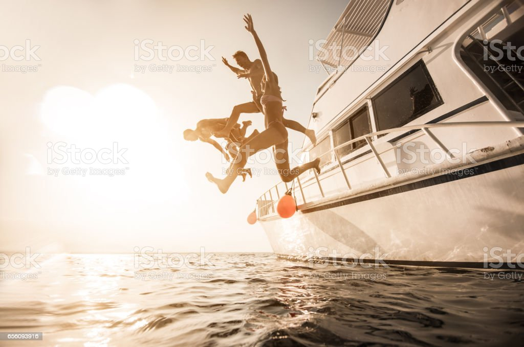 Playful people jumping from the boat into the sea. stock photo