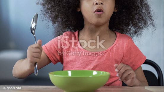 Playful preschool girl asking for dinner, sitting at table with spoon, nutrition