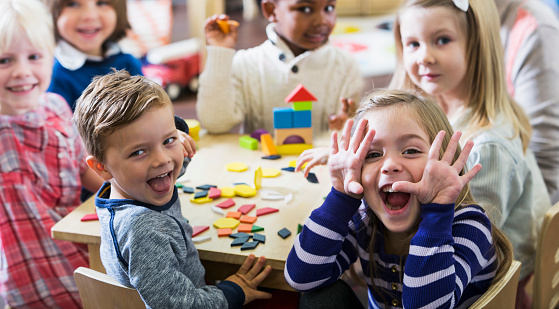 A multiracial group of preschoolers or kindergarteners having fun in the classroom.  Six children are sitting around a little wooden table playing with colorful wooden block and geometric shapes.  The playful little girl in the foreground is making a silly face at the camera.