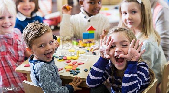 istock Playful preschoolers having fun making faces 473032112