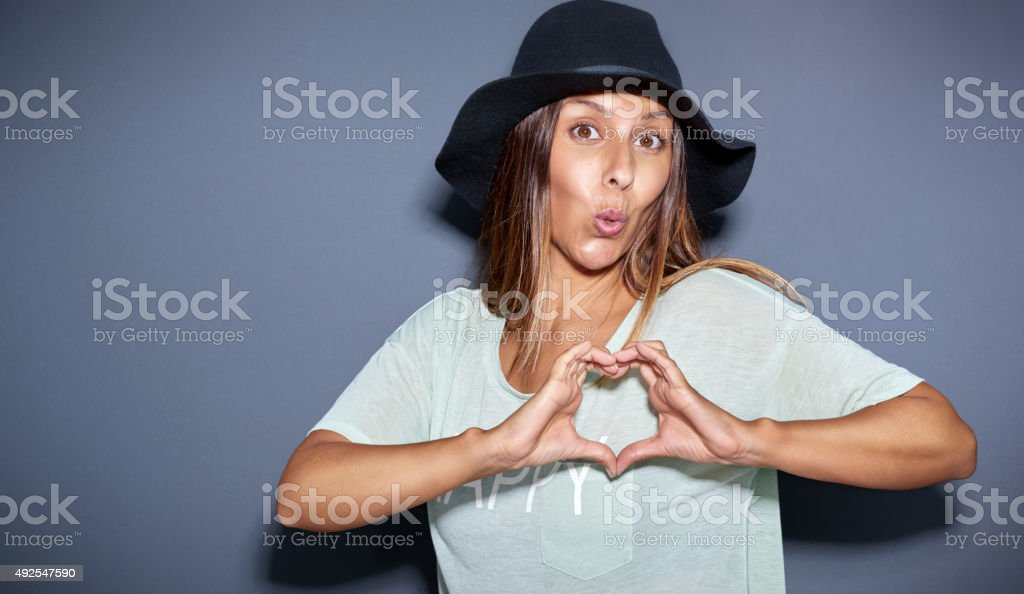 Playful romantic young woman making a heart sign stock photo