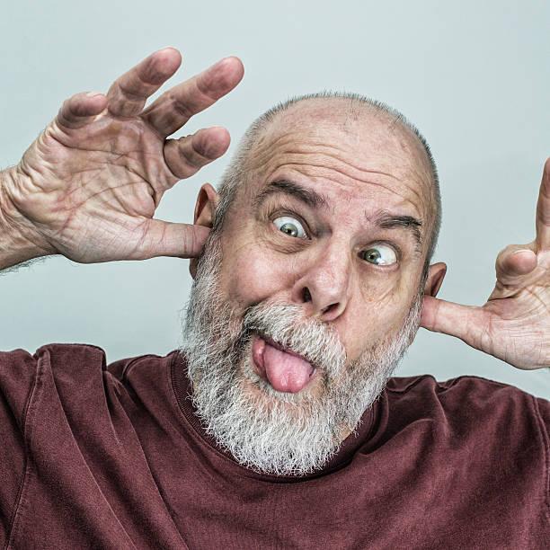verspielte senior erwachsener mann bleiben sie auf der zunge machen lustiges gesicht - geek t shirts stock-fotos und bilder
