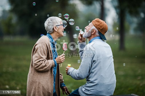 Happy mature couple having fun with bubble wand in the park.