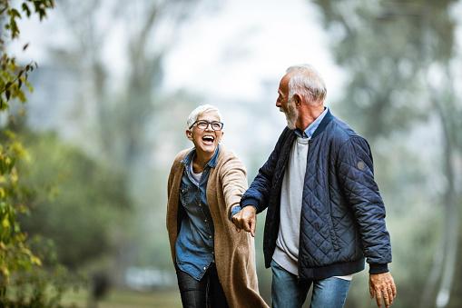 Playful senior couple having fun in the park.