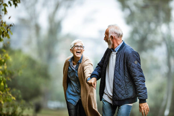Playful senior couple having fun in the park. Cheerful senior couple having fun in the park. Focus is on woman. Copy space. lifestyles stock pictures, royalty-free photos & images