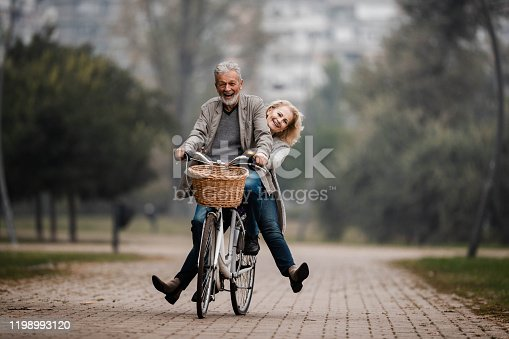 Happy mature couple having fun on a bicycle in autumn day at the park. Copy space.