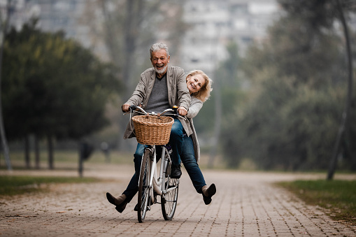 Playful senior couple having fun on a bike in autumn day.