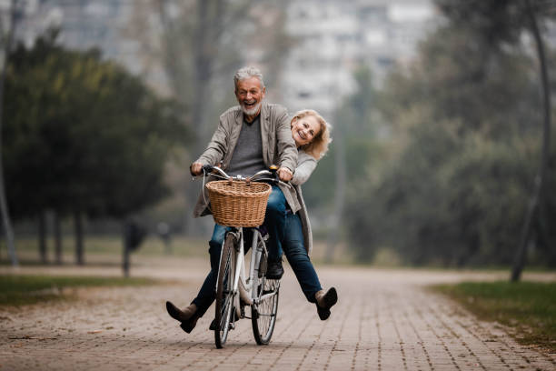 Playful senior couple having fun on a bike in autumn day. Happy mature couple having fun on a bicycle in autumn day at the park. Copy space. young at heart stock pictures, royalty-free photos & images