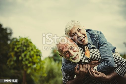 Happy mature couple having fun while piggybacking in the park. Copy space.