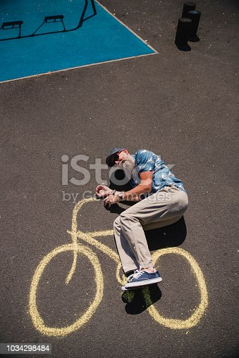 A senior man is lying on the ground on a yellow chalk bicycle.