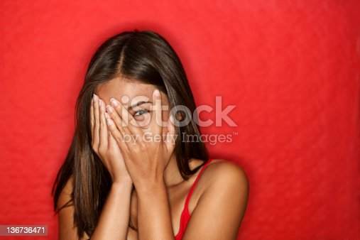 Playful shy woman hiding face laughing timid. Cute Chinese Asian / Caucasian woman smiling happy through hands. Red background.amazement - woman excited looking to the side. See more: