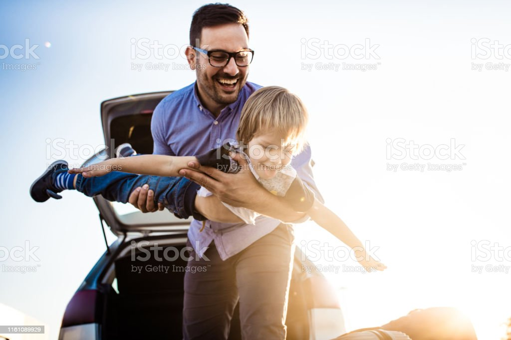 Happy father playing with his small son on the street. Focus is on...