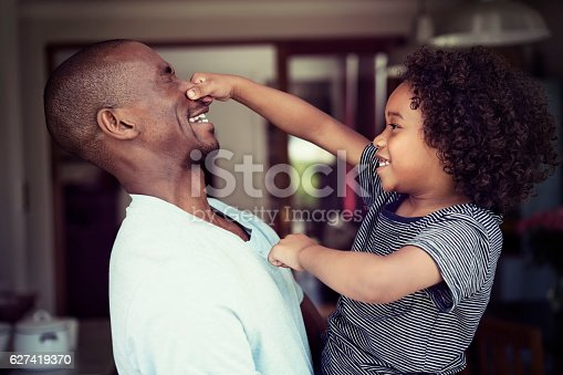 A photo of playful father and son at home. Side view of happy boy pulling man's nose. Both are in casuals.
